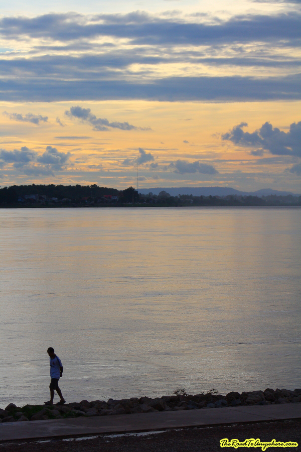Man walking along the Mekong River at Sunset in Vientiane, Laos