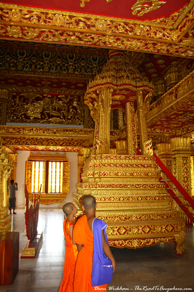Two young monks admiring a beautiful pedestal that houses the Pha Bang in Luang Prabang, Laos