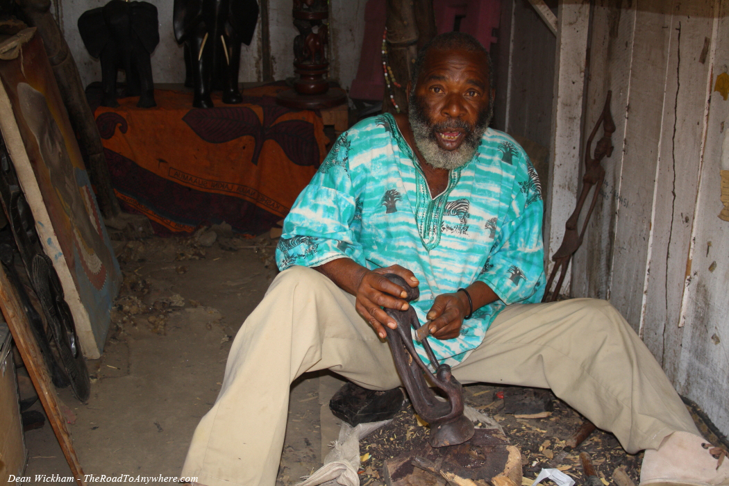 Man carving wooden sculptures at a market in Arusha, Tanzania