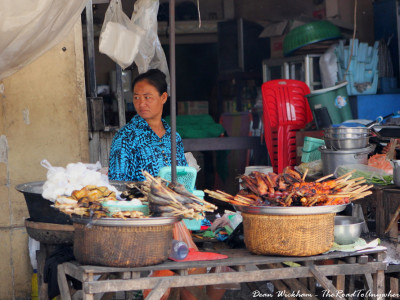 A lady selling grilled meat skewers in Kampong Cham, Cambodia