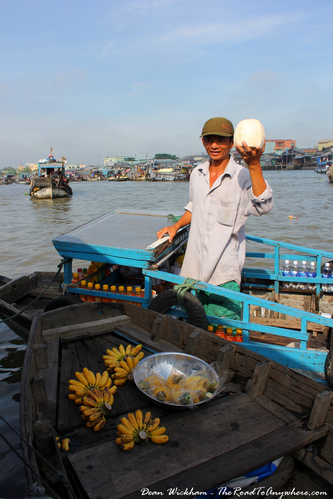 A man selling coconuts at Cai Rang Floating Market in the Mekong Delta, Vietnam