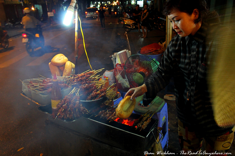 Lady selling grilled meat skewers in Hanoi, Vietnam
