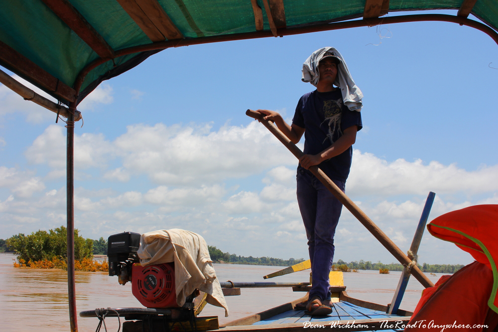 Man steering a boat on the Mekong River in Cambodia