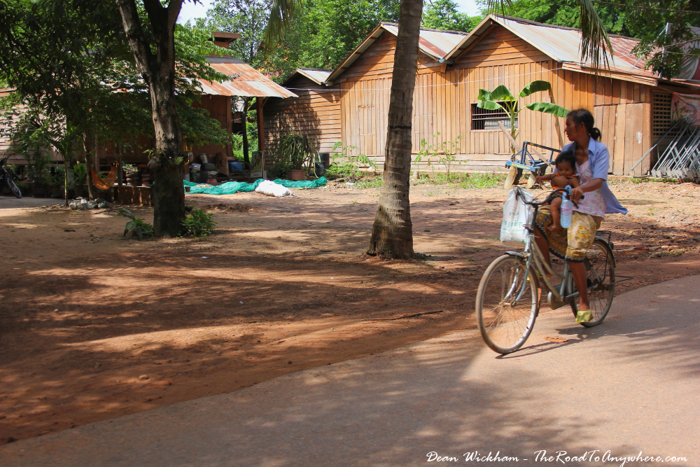A lady holds her baby while riding a bicycle at a village in Western Cambodia