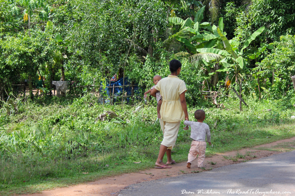 A mother walking along a road with her two children in Cambodia