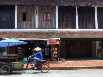 A man on his motorcycle cart travels past some old wooden shopfronts in Luang Prabang, Laos