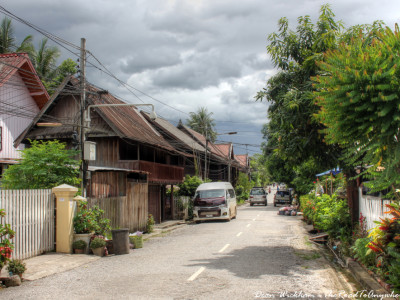 Old wooden houses and modern cars in Luang Prabang, Laos