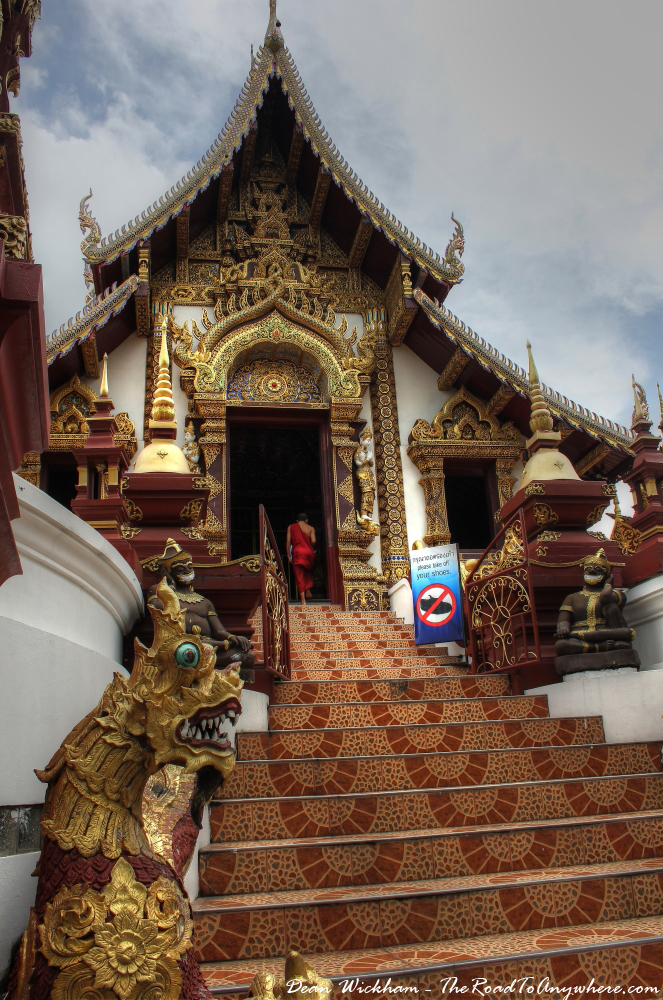 A monk climbs the stairs to Wat Monthian in Chiang Mai, Thailand
