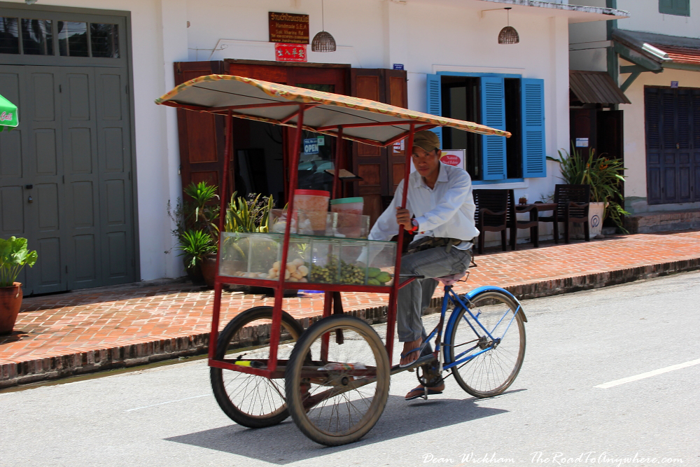 A man cycling his fruit cart through Luang Prabang in Laos